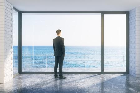 balcony window: Businessman in empty loft room with big window in floor and ocean view