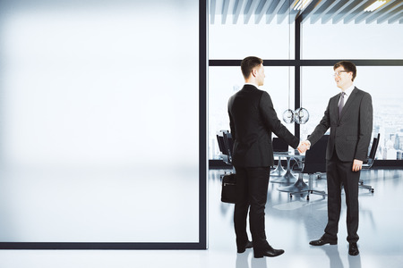 business  deal: Business partners shake hands in modern conference room with blank white wall, mock up