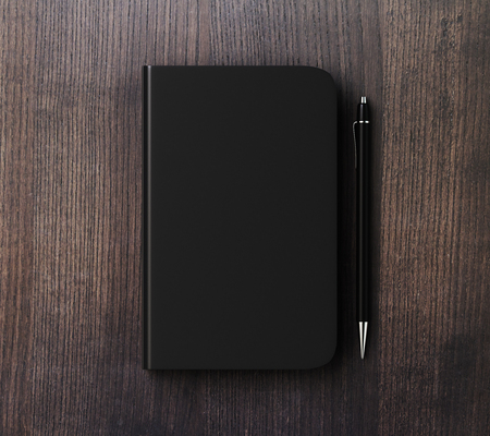 diary cover: Blank black diary cover with pen on brown wooden table, mock up Stock Photo