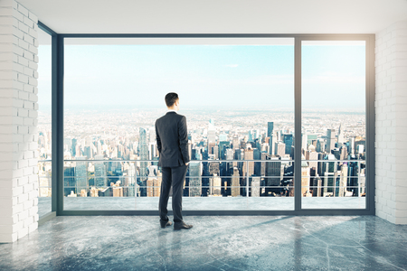 Businessman in empty loft style room with concrete floor and city view