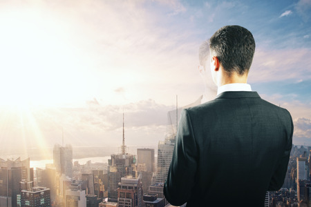 out of business: Businessman looking at sunrise from the top of building Stock Photo