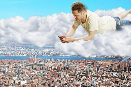 megapolis: A man with smartphone laying on clouds above the megapolis city Stock Photo