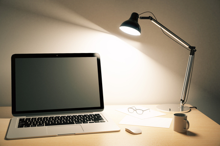 lamp: Blank black laptop screen with coffee mug and a lamp on wooden table, mock up