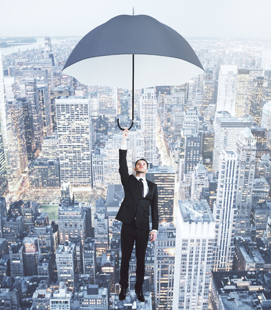 megapolis: Businessman flying with umbrella above evening megapolis city concept Stock Photo