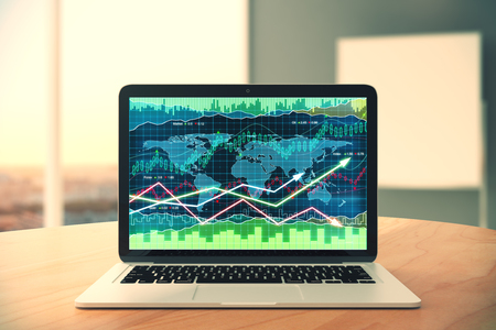 Laptop screen with business chart with arrows on wooden table