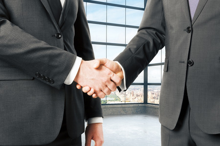 negotiation business: Business partners shake hands in empty loft office