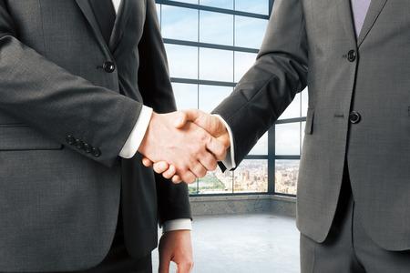 Zakelijke partners schudden handen in het lege loft kantoor