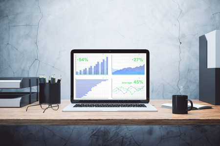 laptop screen: Business chart on laptop screen with other accessories on wooden table Stock Photo