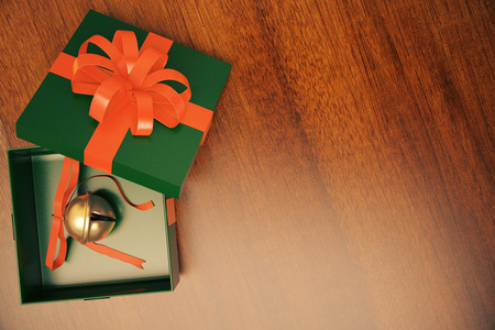 jingle bell: Green gift box with jingle bell inside on wooden floor