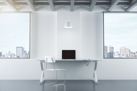 design office: Empty white interior with table, chair, brick wall and windows, and laptop