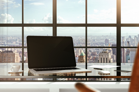 Blank laptop on a glass table in a modern office and city views from the windows Standard-Bild