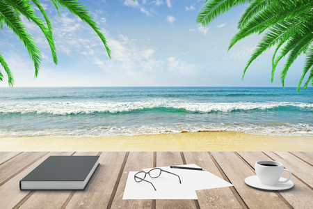 lapiceros: Diario, papeles en blanco y taza de café en el banco de madera en el fondo de la playa