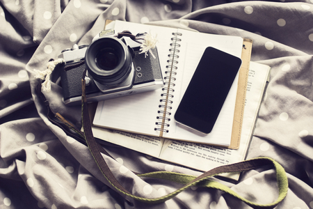 publicist: Vintage camera with blank black cell phone and blank diary, mock up