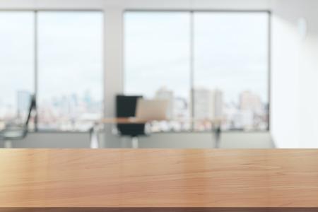 Houten tafel in lichte kantoor met panoramische ramen