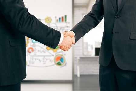 shaking: Two businessman shaking hands in office