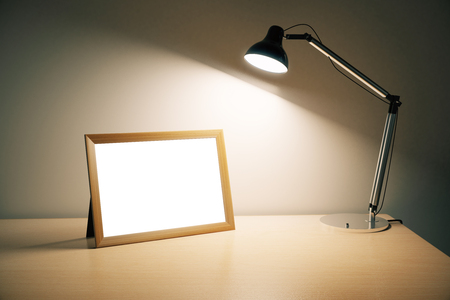 old desk: Blank picture frame with lamp on wooden table, mock up