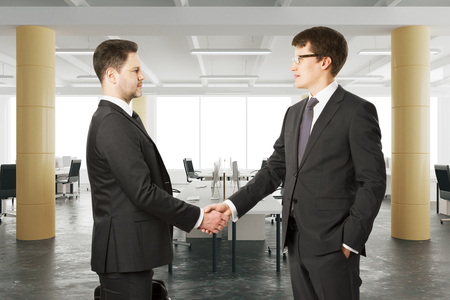 business table: Business partners shake their hands in modern open space office