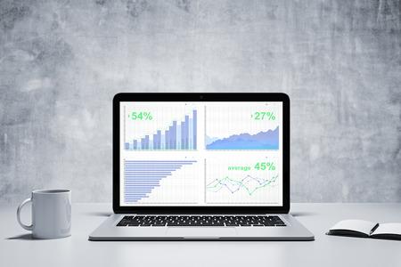 Bedrijfs grafiek op een scherm van de laptop met een kopje koffie en dagboek op witte tafel en betonnen wand Stockfoto