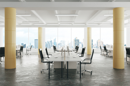 Modern open space loft office with concrete floor, big windows and pillars