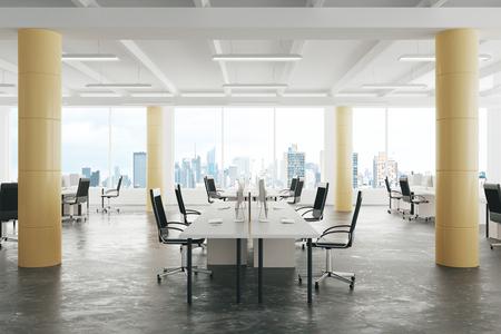 Moderne open ruimte loft kantoor met betonnen vloer, grote ramen en pilaren
