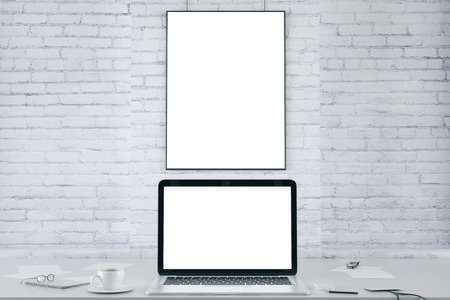 blank photo: Blank picture frame on white brick wall and blank white laptop screen, mock up Stock Photo