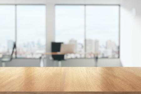 mesa de madera en la oficina soleada con grandes ventanas Foto de archivo