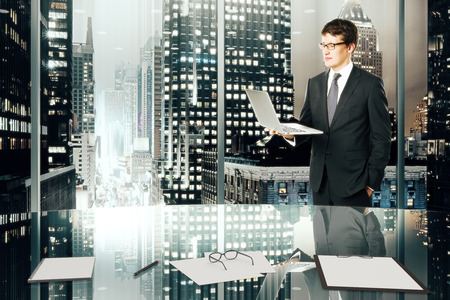 megapolis: Businessman with laptop in modern office with night megapolis city view