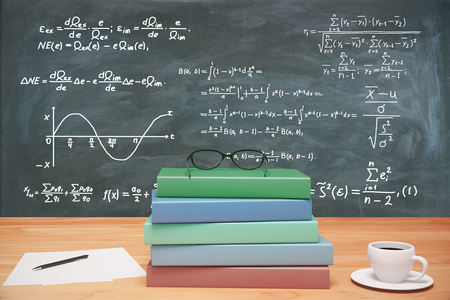 stack of papers: Pile of colorful books, eyeglasses and cup of coffee on wooden table at blackbooard with equations