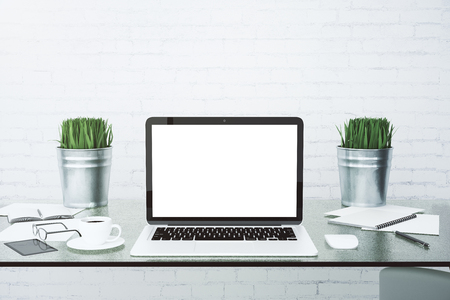 Blank white laptop screen on glassy table with cup of coffee at brick wall background, mock up Stock Photo