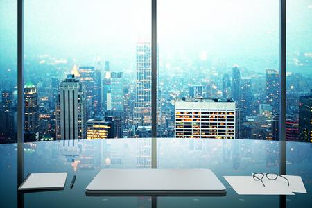 ガラス テーブルは、近代的なオフィスのラップトップと夜のメガポリス シティー ビュー 写真素材