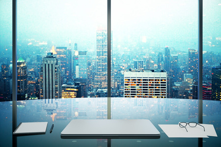 Modern office with glassy table, laptop and night megapolis city view Foto de archivo