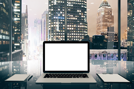 megapolis: Blank white laptop screen on glassy table in modern office with night megapolis city view, mock up Stock Photo