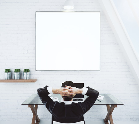 Businessman resting on a chair and looking at blank white picture frame on white brick wall, mock up Фото со стока