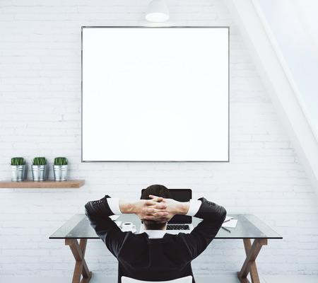 Geschäftsmann auf einem Stuhl stillsteht und Blick auf leere weiße Bilderrahmen auf weiße Wand, Mock-up Standard-Bild - 49255444