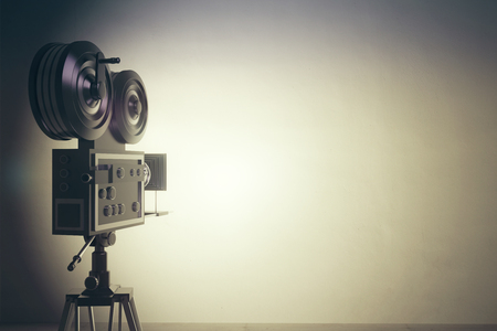 Old style movie camera with white wall, vintage photo effect