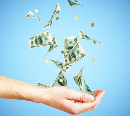 Human hand with money and coins falling at blue background Stock Photo