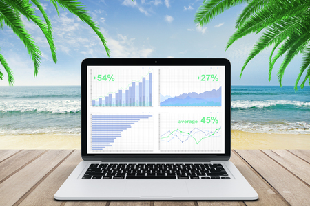 wooden bench: Business chart on laptop screen on wooden bench at ocean beach background