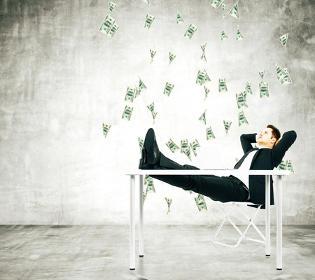 raining: Businessman on a chair in loft room with money falling from the ceiling Foto de archivo