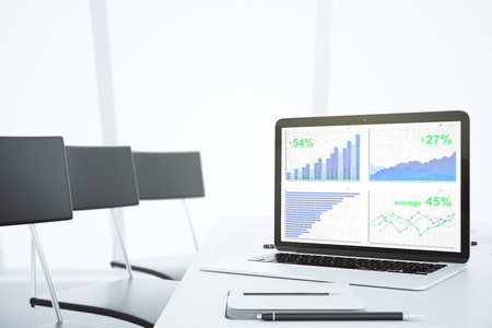 Business graph on laptop screen in modern light conference room