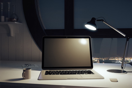 Black blank laptop with cup of coffee and lamp at night