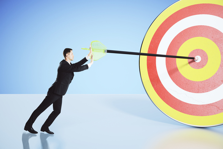 stubbornness: Move towards your goal concept with businessman pushing an arrow into the bullseye Stock Photo