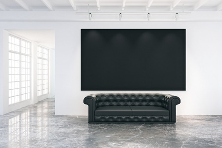 concrete room: Blank black poster on white wall in loft room with black leather sofa and big windows, mock up
