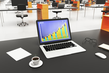 office accessories: Laptop with business graph on a screen, cup of coffee and office accessories in open space office Stock Photo