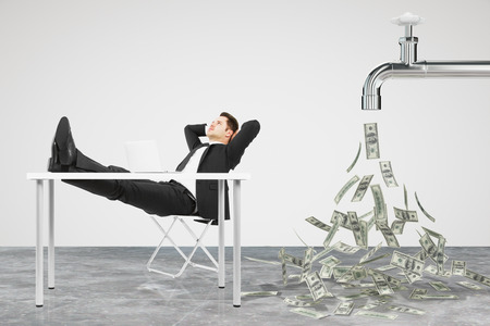 Businessman resting on a chair and faucet from which the money flow Standard-Bild