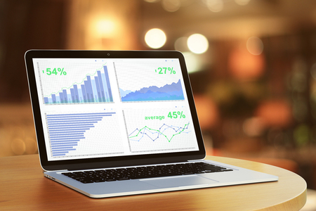 laptop screen: Business chart on laptop screen on round wooden table