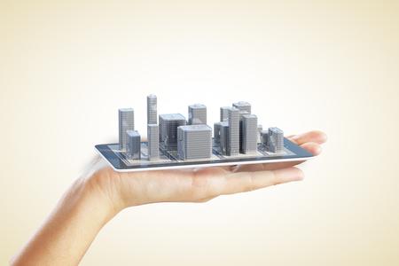 手は、携帯電話で市街地の計画を示しています