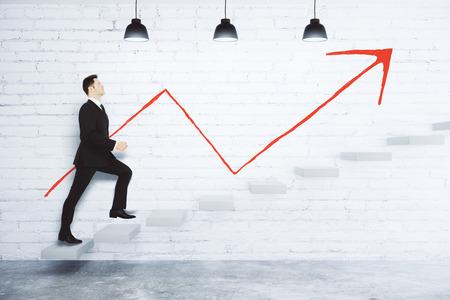 Succes concept met zakenman het beklimmen van de trap en rode pijl op witte bakstenen muur Stockfoto