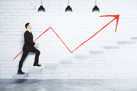 Success concept with businessman climbing the stairs and red arrow on white brick wall