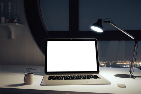 Blank white laptop screen on the table and lamp in the office with round window at night, mock up