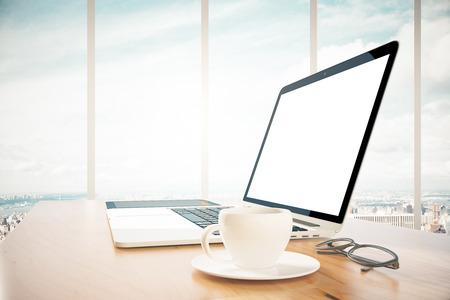 Blank Laptop-Bildschirm auf einem hölzernen Schreibtisch und einer Tasse Kaffee, Mock-up